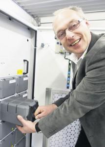 Elektromeister Peter Henning zieht an einem Stromspeicher eines von mehreren Strom-Speichermodulen heraus