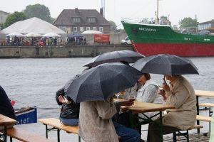 """Beinhart im Nehmen: Beim Hafenfest in Harburg gibt es kein schlechtes Wetter, nur unpassende Kleidung - oder einen Schirm. Im Hintergrund: Die """"Greundiek"""" aus Stade. Foto: Heingerd Detjen"""