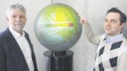"""Professor Dr. Volker Gollnick (links) und Dr. Florian Linke vor dem Globus, der die Globalwirkungen des Flugverkehrs darstellt und im """"Goldfisch""""-Foyer, Blohmstraße 20, im Harburger Binnenhafen steht. Hier ist das Institut zu Hause."""