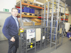 Rainer Kalbe steht vor bereits vormontierten Modulen, die in der Werkstatt am König-Georg-Stieg in Wilhelmsburg für Bäder in einer Reihenhauszeile vorbereitet worden sind. Fotos: Wolfgang Becker