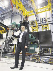 Dr. Dirk Niermann steht in der Versuchsanlage, die im Maßstab 1:1 Viertelschalen von CFK-Rümpfen zusammenfügen kann. Die Schalen werden von Vakuumsaugnäpfen gehalten, die wiederum auf Hexapoden (sechsbeinigen Robotern)sitzen. Die größte Herausforderung besteht im Datenmanagement, denn der Prozess des Zusammenfügens wird über unzählige Messdaten gesteuert. Foto: Wolfgang Becker