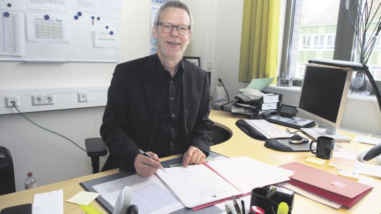 Wolfgang Bruhn bei einer seiner letzten Amtshandlungen am Schreibtisch im Schulleiterbüro: dem Unterschreiben von Zeugnissen. Foto: Wolfgang Becker