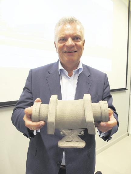 Prof. Dr. Claus Emmelmann zeigt den Einfüllstutzen für das Militärfl ugzeug A400M. Gedruckt ist es halb so teuer wie konventionell gefertigt. Fotos: Wolfgang Becker